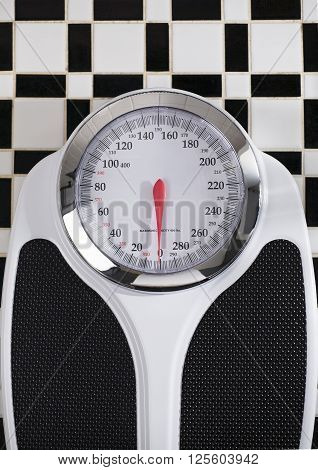 vertical photograph of a bathroom scale on black and white tile flooring