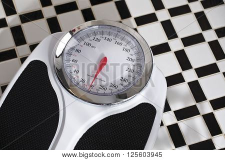 horizontal photograph of a bathroom scale on black and white tile flooring