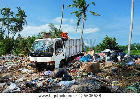 BALI, INDONESIA - April 10, 2016: Amid contaminated agricultural land, a refuse worker dumps waste at an illegal waste-recycling center in Pejeng on April 10, 2016 in Ubud, Bali, Indonesia.
