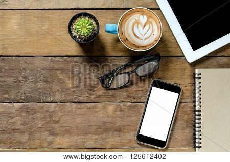Office desk table with tablet coffee cup smartphone and notebook.Top view with copy space