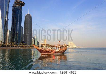 A pleasure dhow sailing in Doha Bay, Qatar, under the shadow of the city's huge towers, January 2016