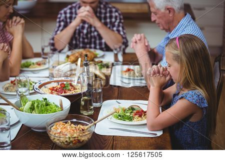 Multi generation family praying with granddad sitting at dining table in home