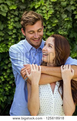 Front view of happy couple hugging at front yard
