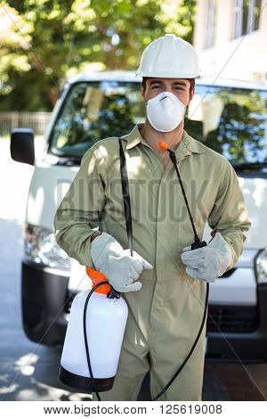 Portrait of worker with pesticide sprayer while standing by van