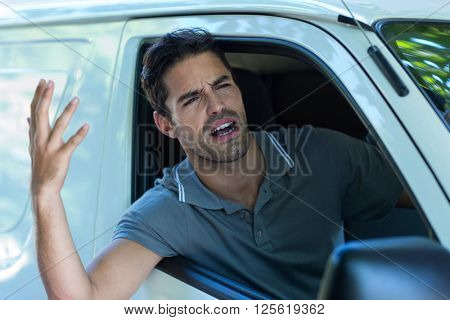 Irritated man gesturing while sitting in car