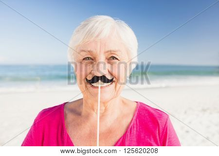 Senior woman with fake mustache on the beach