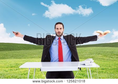 Unsmiling businessman sitting with arms outstretched against blue sky over green field