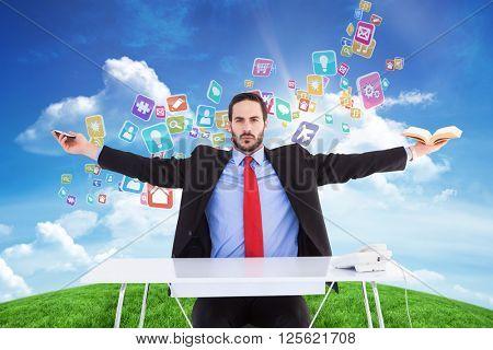 Unsmiling businessman sitting with arms outstretched against green hill under blue sky