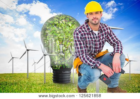 Crouching handyman holding power drill against wind turbines and bulb full of leaves