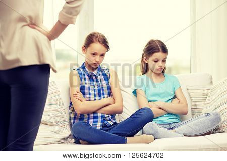 people, children, misbehavior, friends and friendship concept - upset feeling guilty or displeased little girls sitting on sofa and angry mother at home