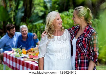 Smiling mother-in-law and daughter-in-law standing at yard
