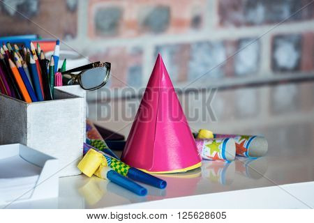 Party horn, birthday hat, pen holder and spectacle on desk in office