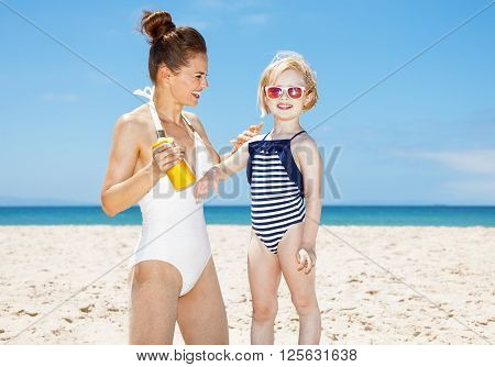 Happy Mother Applying Sunscreen On Child's Arm At Sandy Beach