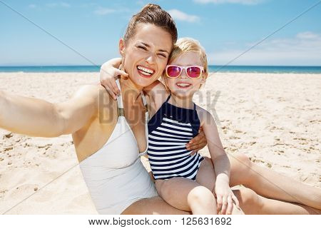 Smiling Mother And Daughter In Swimsuits Taking Selfies At Beach