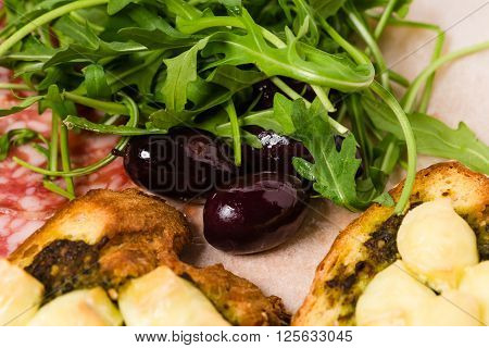 Traditional tuscan antipasto platter with kalamata olives and fresh arugula. Macro. Photo can be used as a whole background.