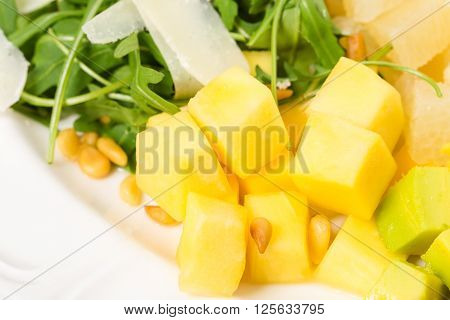 Jumbo shrimp salad with mango and arugula topped with pine nuts and parmesan cheese. Macro. Photo can be used as a whole background.