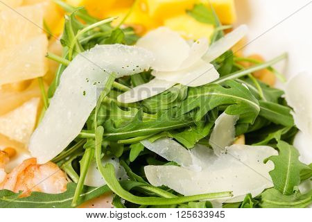 Closeup of arugula and parmesan in jumbo shrimp salad with mango and avocado. MAcro. Photo can be used as a whole background.