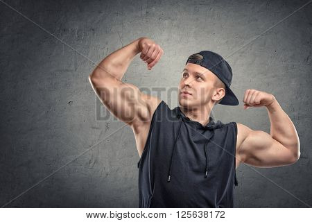 Portrait of young muscular man flexing his biceps and looking away. Body power.