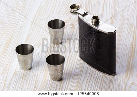 Metal flask trimmed leather and three metallic, sturdy shot glasses on a wooden background
