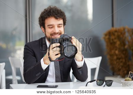 Young man photographer working at cafe, using dslr camera. His laptop at the table.
