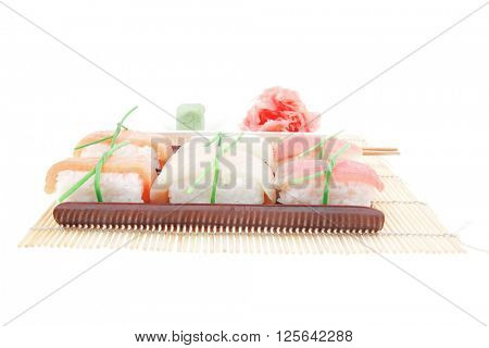Japanese Cuisine - Different Types of Nigiri Sushi : Tuna (maguro) Salmon (sake) and Eel (unagi) with Wasabi and Ginger on bamboo mat isolated over white background