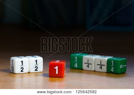 Fraction dices on wood table shown whole and fraction numbers, dark background and selective focus on red dice