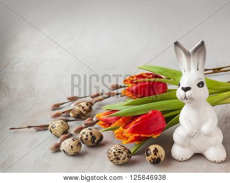 Easter bouquet with tulips and willow branches near figure Easter bunny on a gray background (mass production)