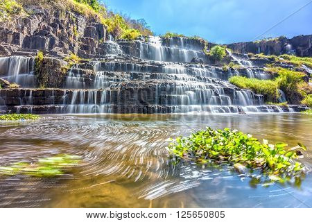 Ponguor Waterfall in the sun with water flowing down the stairs step by creating its folds like silk, beneath the swirl of all scraped up the beauty of nature in Lam Dong, Vietnam