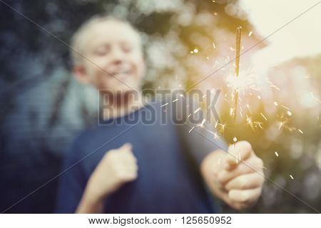 Child holding a sparkler, blurred shallow focus image, focus on sparks, Instagram toned image
