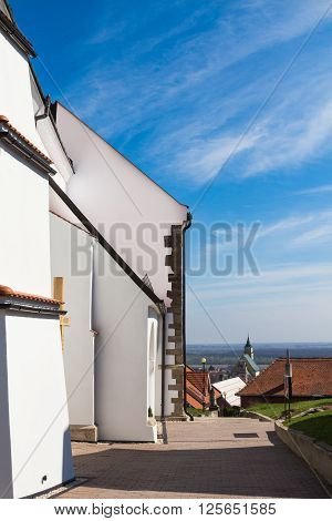 Side part of the gothic christian church built on a hill in village Svaty Jur Slovakia.View on a village and horizon of the nature around. Blue sky with clouds. poster