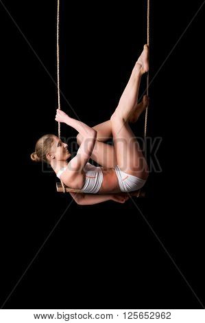 Young Woman Gymnast On A Trapeze Over Black Background