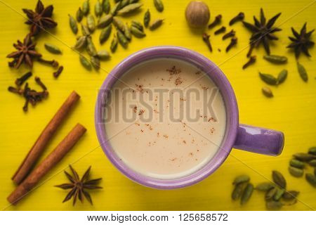 masala chai tea with spices and star Anise cinnamon stick nutmeg and cardamon on the yellow background