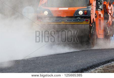 Road roller flattening new asphalt, orange roller