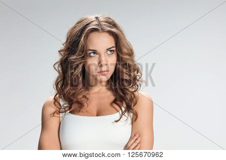 The portrait of disgusted and disaffected woman on gray