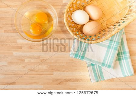 Eggs In Braided Bucket On Towel And Raw Eggs In Glass Pialat On Light Wooden Background With Copyspa