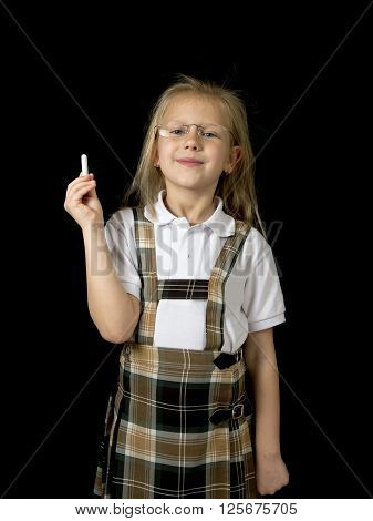 young sweet junior schoolgirl with blonde hair standing happy and smiling isolated in black background holding chalk wearing school uniform in children education success and fun