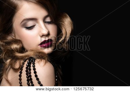 Beautiful brunette in a Hollywood manner with curls, dark lips. Beauty face. Picture taken in the studio.