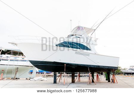 White small motor boat at dry shipyard for maintenance in Phuket Thailand