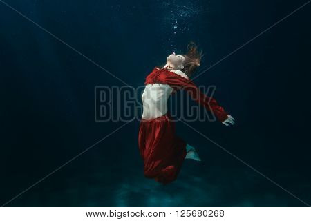 Woman in a red dress on the bottom underwater.