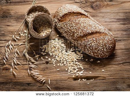 Oat whole grain bread rolled oats and oat plants on rustic wooden background.