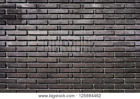 Black brick wall background texture close up