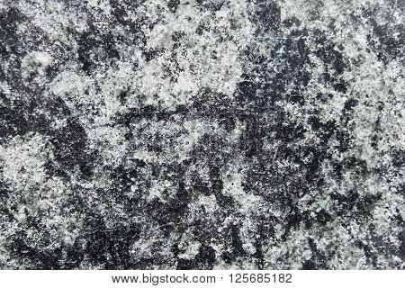 Black granite wall background texture close up