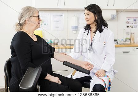 Doctor Touching Senior Patient's Arm Before Blood Test