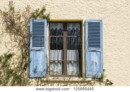 Beige wall with blue shutters window close up