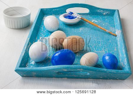 Wooden eggs paints and brush on a tray. Creativity Easter