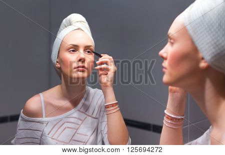 Young woman applying eyeliner in front of the mirror.