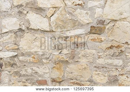 Beige stone mosaic wall background texture close up