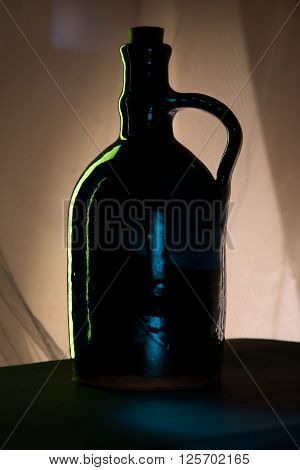 Silouette of bottle for wine or water in shadow.