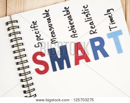 SMART Goals in notebook and pen on wood background (Business Concept)