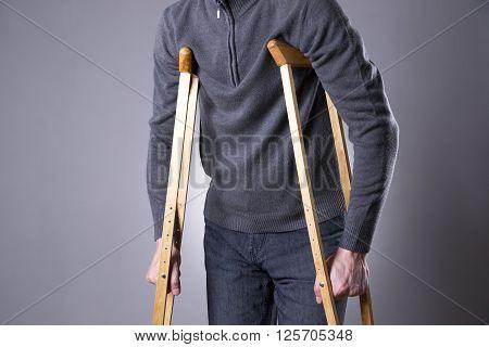 Man on crutches on a gray background. Studio shot